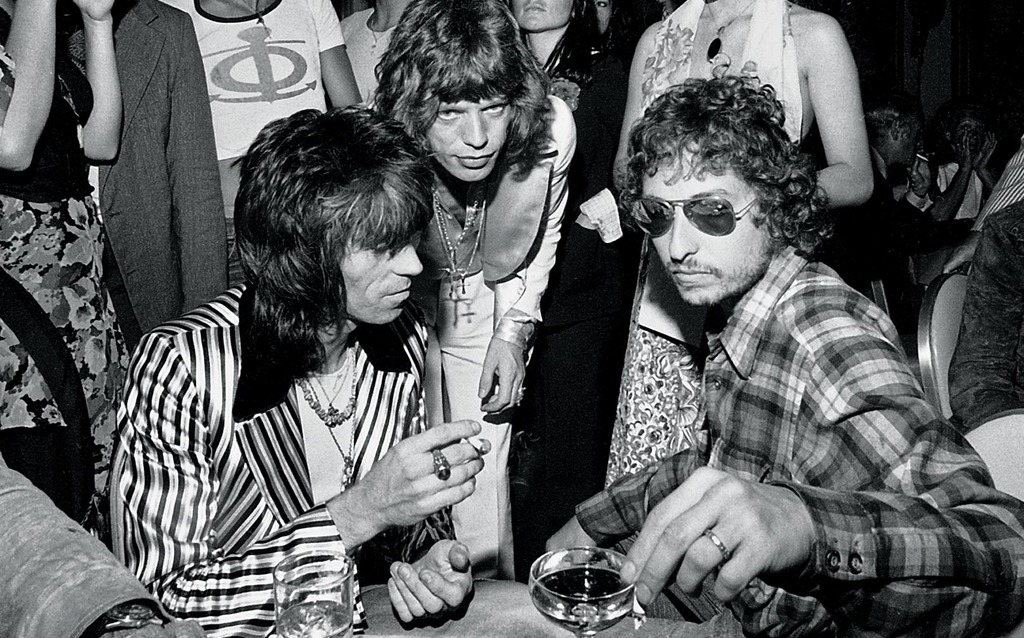 Bob Dylan in mirrored aviator sunglasses, Keith Richard in Granny Takes a Trip Jacket, Mick Jagger hovering overhead