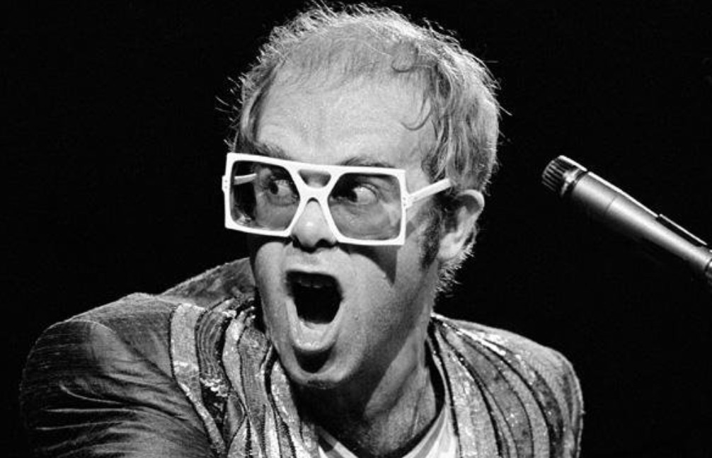Elton John wearing square sunglasses by Anglo American, circa 1975