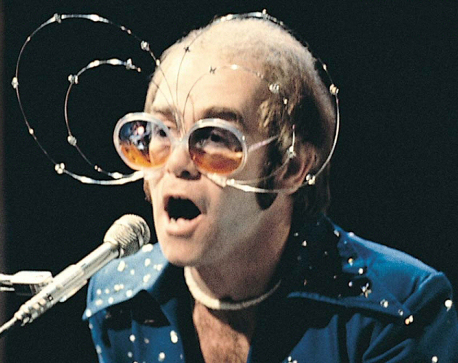 Elton John wearing the famous May sunglasses.   They go nicely with the rhinestones on his shirt collar.