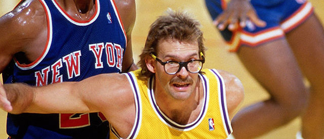 Kurt Rambis blocking out a Knick for a rebound.