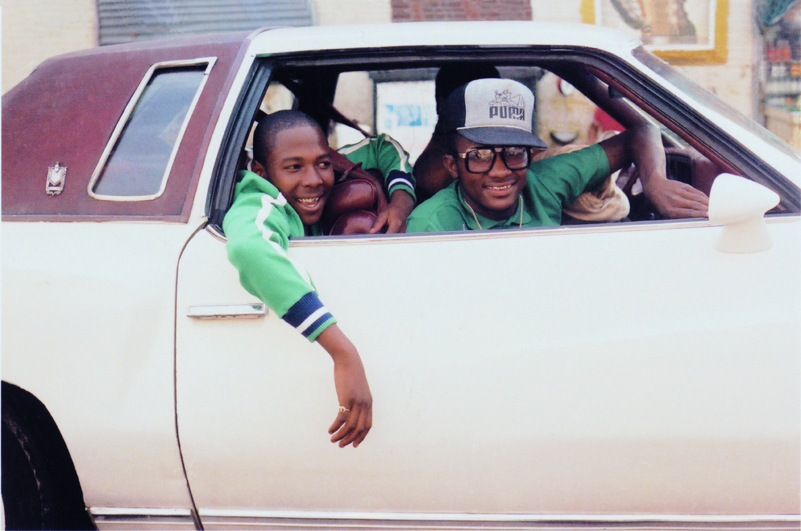 Cazal 616 eyeglasses and a Puma baseball hat. The car looks like a 1977 Oldsmobile Cutlass. Photo by Jamel Shabazz.