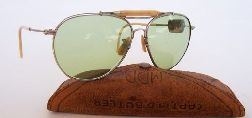 WWII aviator sunglasses. Frame by Bausch & Lomb, case by American Optical. Captain M.D. Butler has inscribed his name on the case and brow bar. Note the field repair on the left temple.
